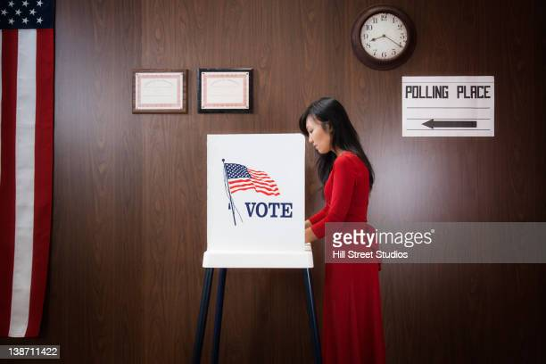 Asian voter voting in polling place