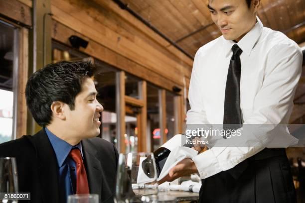Asian waiter showing wine to customer