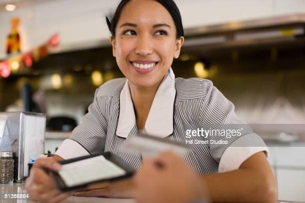 Asian waitress handing bill to customer