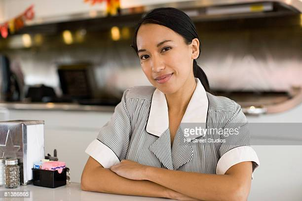 Asian waitress leaning on counter