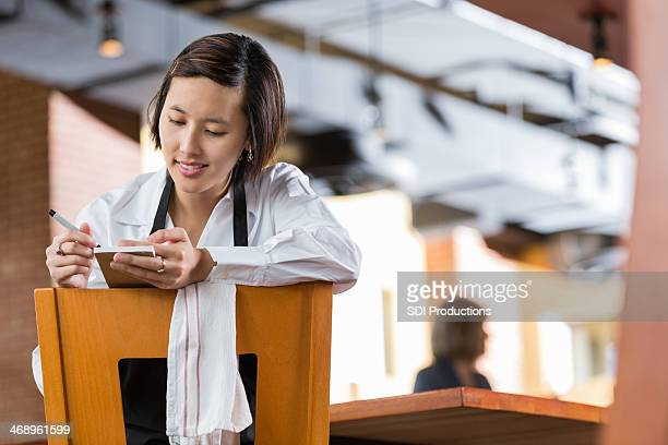 Asian waitress looking at tickets in restaurant after closing time