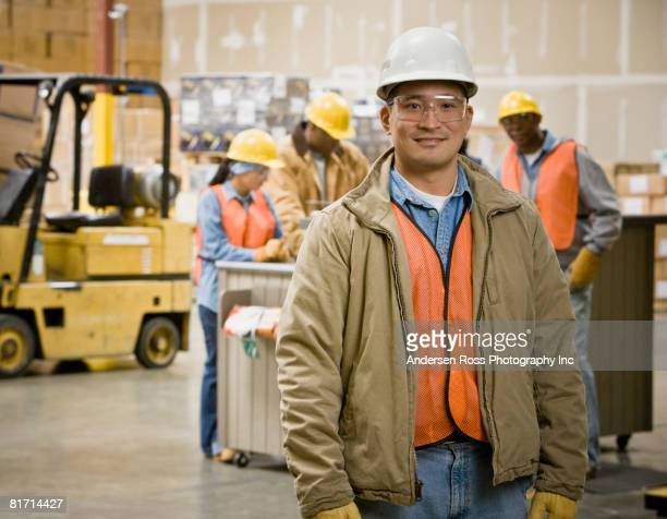 Asian warehouse worker in front of coworkers