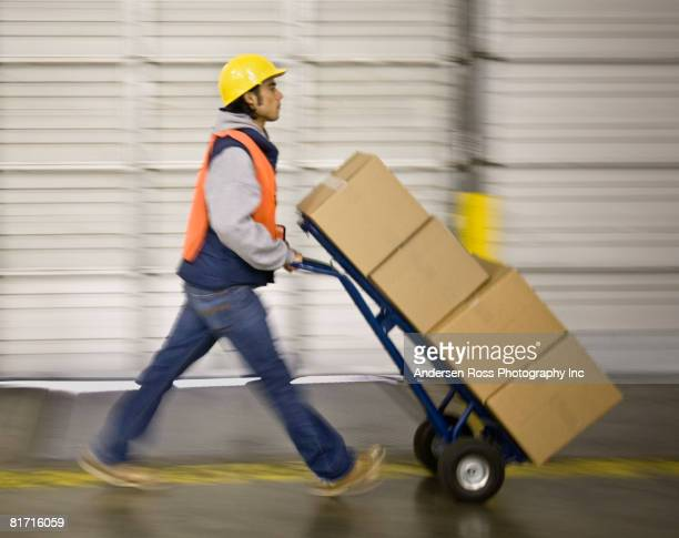 asian warehouse worker pushing boxes on hand truck - sack barrow stock pictures, royalty-free photos & images