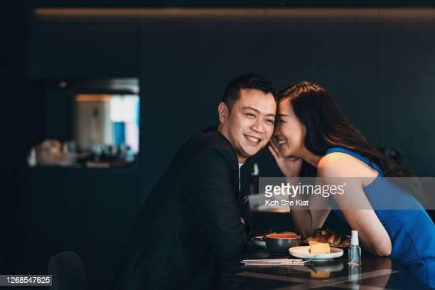 femme asiatique chuchotant une agréable surprise au mari au-dessus d'un repas - annonce grossesse photos et images de collection