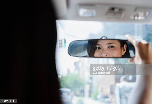 Asian woman adjusting rear-view mirror