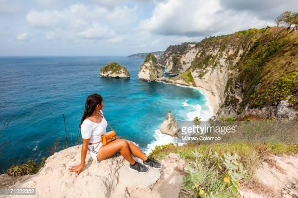 asian woman admiring diamond beach, nusa penida - baia foto e immagini stock