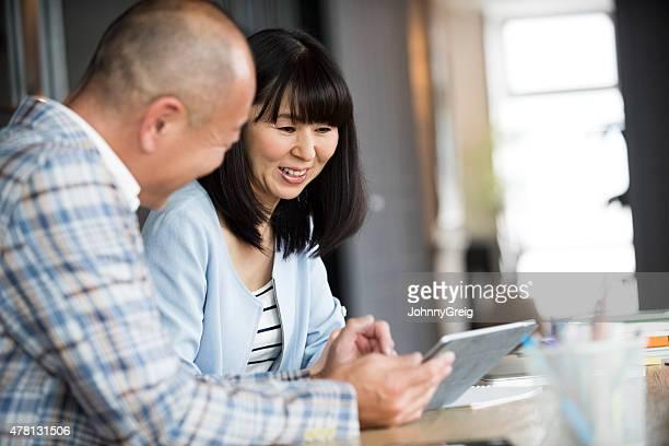 アジアの女性と男性のデジタルタブレット - 中年カップル ストックフォトと画像