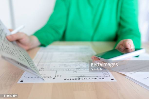 asian woman applies for the covid-19 vaccination by using a smartphone - department of health stock pictures, royalty-free photos & images