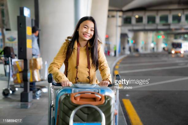 asian woman are carrying baggage trolleys within the airport. - korean teen stock pictures, royalty-free photos & images