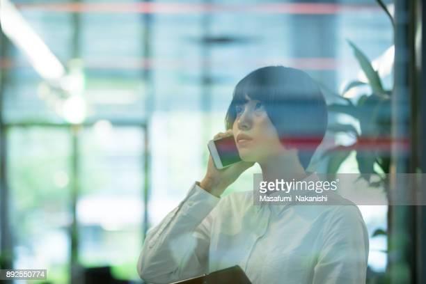 アジアの女性は、事務所の窓からビルでスマート フォンを使用しています。