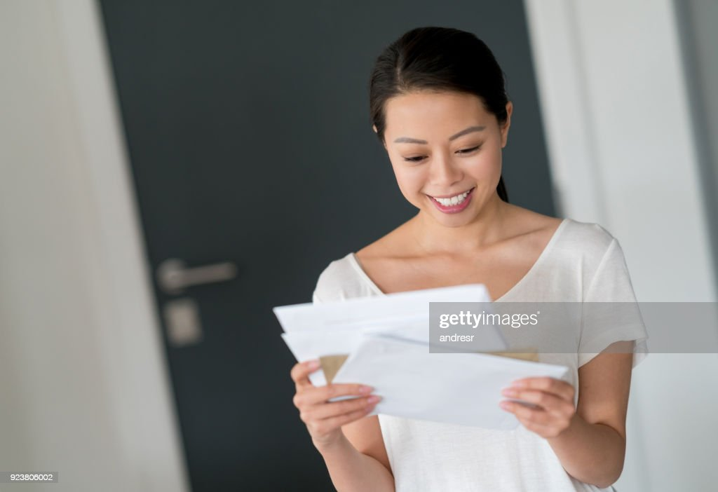Asian woman at home checking her mail : Stock Photo