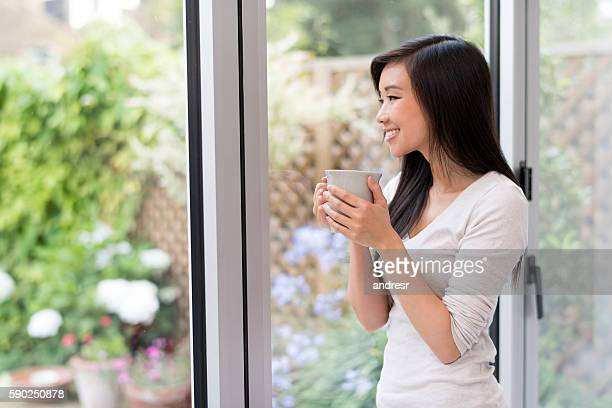 Asian woman at home drinking coffee