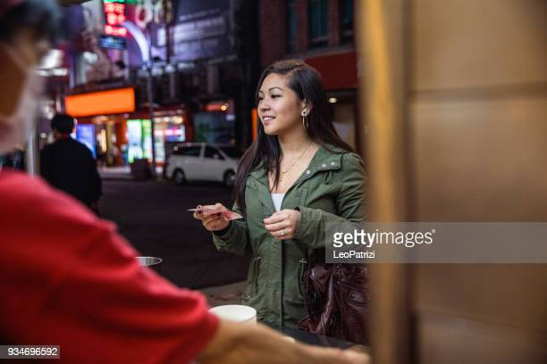 Asian woman at night in downtown Taipei - Taiwan buying street food from a vendor
