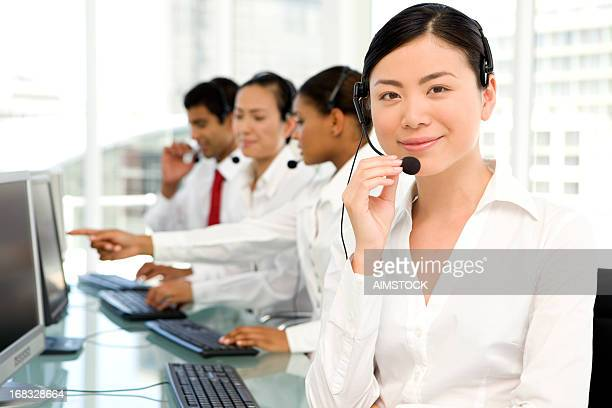 Asian woman at work in busy Call center