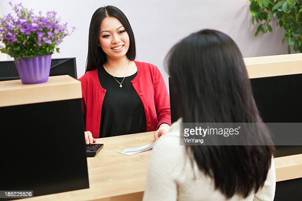 asian woman bank teller serving customer approaching retail banking counter - cashier stock pictures, royalty-free photos & images
