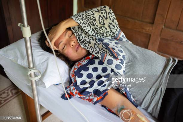 asian woman being treated at home for virus symptoms - dengue imagens e fotografias de stock