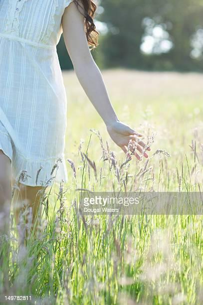 Asian woman brushing hand through grasses.