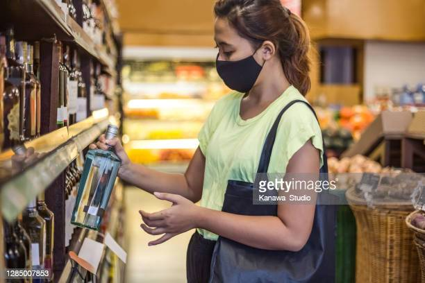 asian woman buying gin alcohol bottle in supermarket - vodka stock pictures, royalty-free photos & images