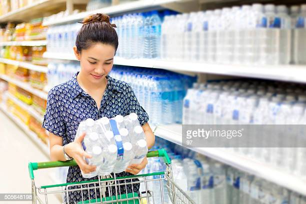 Asian woman buys in the supermarket bottle of water