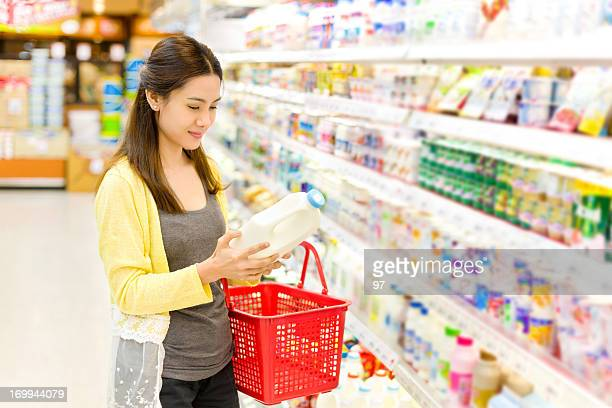 Asian woman buys in the supermarket gallon of milk.