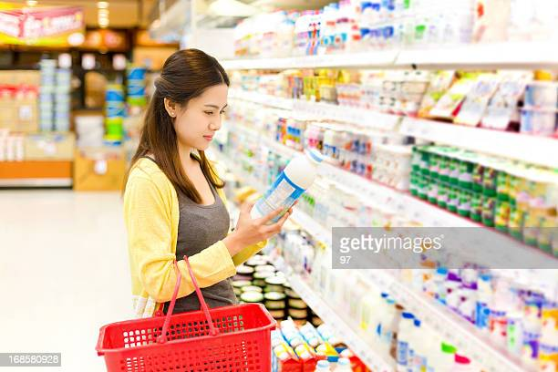 Asian woman buys in the supermarket milk.