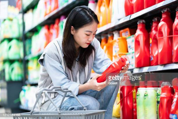 asian woman buys washing powder in supermarket - cleaning agent stock pictures, royalty-free photos & images
