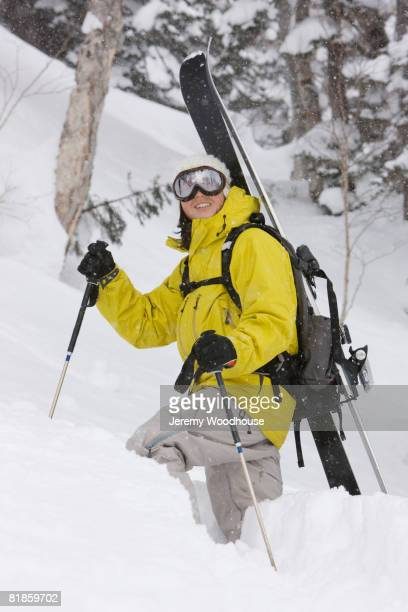 Asian woman carrying skis on back