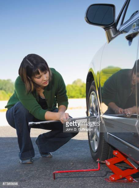 Asian woman changing car tire