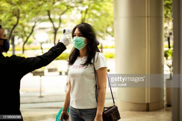 asian woman checked with thermometer to control the temperature required to be checked in quarantine - safety stock pictures, royalty-free photos & images