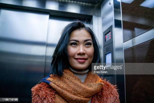 mulher asiática que verific-se para fora no espelho do elevador - elevador - fotografias e filmes do acervo