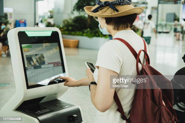 asian woman checking in at the airport using a self check-in machine - kiosk stock pictures, royalty-free photos & images