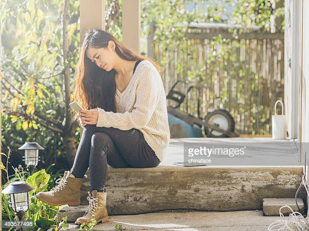 asian woman checking phone messages