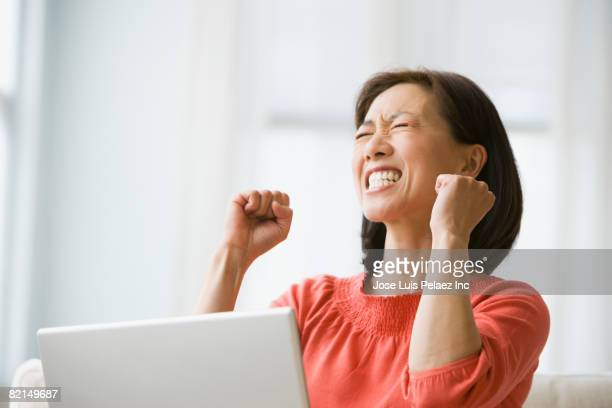 Asian woman cheering next to laptop