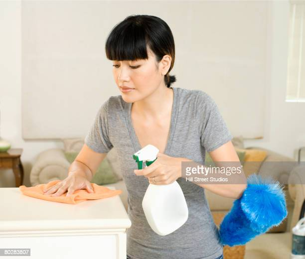 Asian woman cleaning in living room