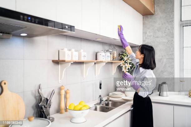 asian woman cleaning the kitchen - washing up glove stock pictures, royalty-free photos & images