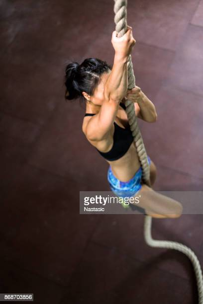 Asian Woman climbing rope in gym