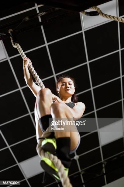 Asian Woman climbing rope