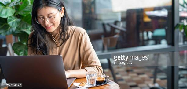 asian woman/ college student using a laptop computer to study remotely at a cafe - hot desking stock pictures, royalty-free photos & images