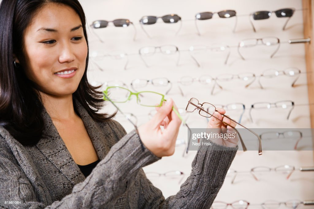 Asian woman comparing eyeglasses : Stock Photo