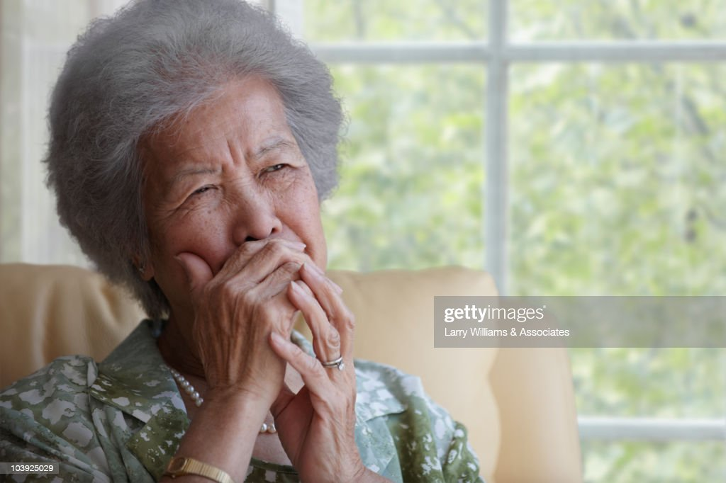 Asian woman covering mouth with hand : Stock Photo