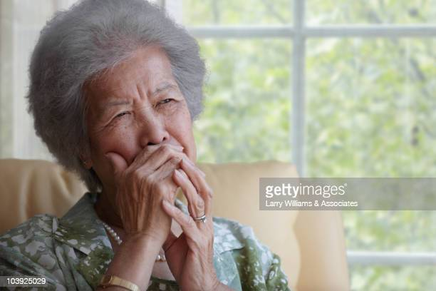 Asian woman covering mouth with hand