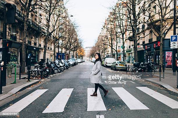 asian woman crossing zebra in paris - pedestrian crossing stock photos and pictures