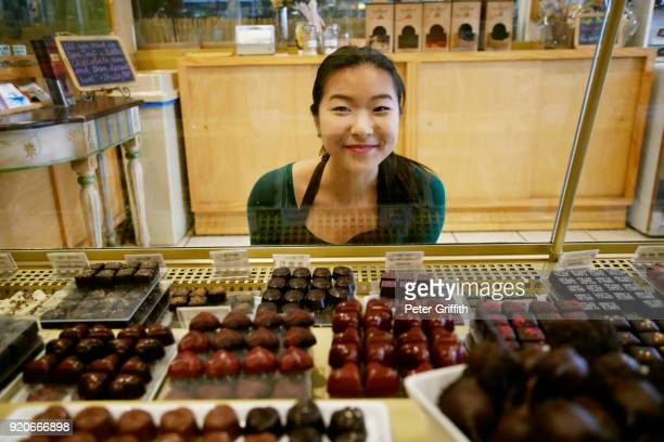 Asian woman crouching near display case in chocolate store