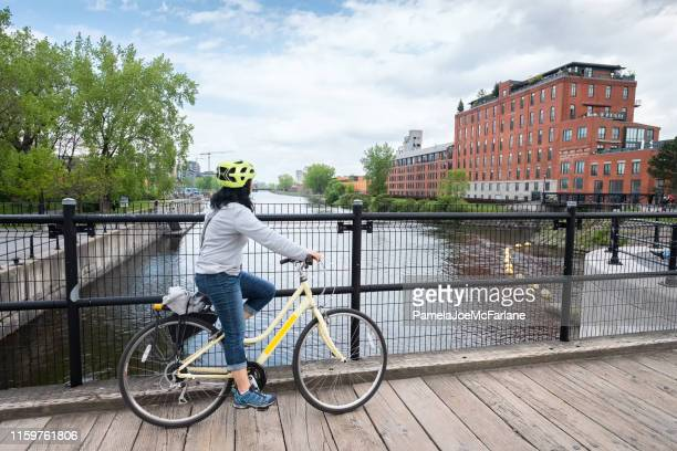 asian woman cyclist enjoying view of lachine canal, montreal, quebec - montréal stock pictures, royalty-free photos & images