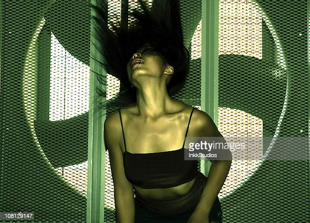 Asian woman dancing infront of industrial fan.