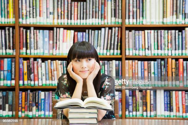 Asian woman daydreaming in library