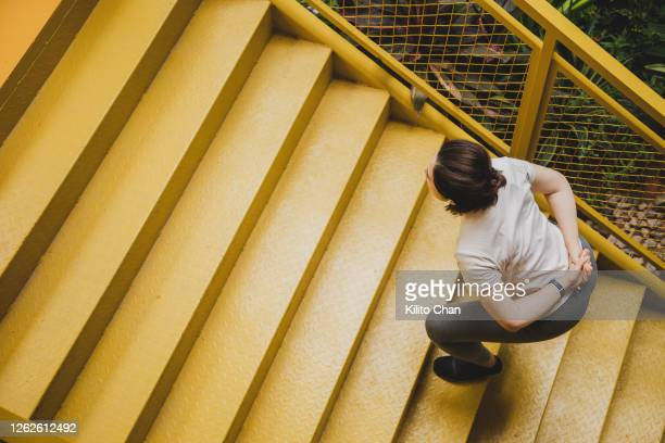 asian woman doing squat on yellow staircase - staircase stock pictures, royalty-free photos & images