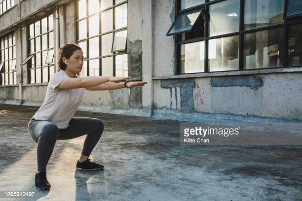 asian woman doing squats while listening to something - 自重トレーニング ストックフォトと画像
