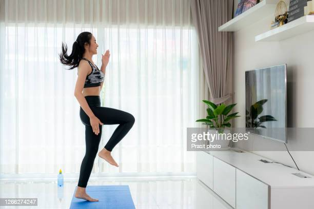 """asian woman doing strength training cardio aerobic dance exercises """"u201chigh knee""""u201d while watching videos fitness workout class live streaming online on a smart tv in the living room at home. - cardiovascular exercise stock pictures, royalty-free photos & images"""