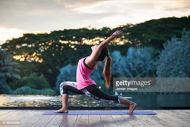 Asian woman doing yoga positions on deck at sunset.